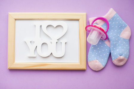 Geschichte des Neugeborenen. Rahmen mit Kopienraum und Kinderspielzeug, Schere, Babyflasche, Nippel, Haarbürste auf violettem Hintergrund. Ansicht von oben