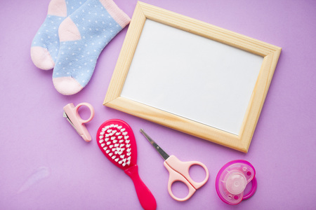 Newborn baby story. Frame with copyspace and children's toys, scissors, baby bottle, nipple, hairbrush on violet background. Top view