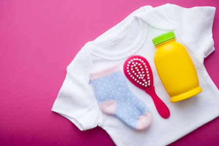 Newborn baby story. T-shirt and children's toys, scissors, baby bottle, nipple, hairbrush on red background. Top view