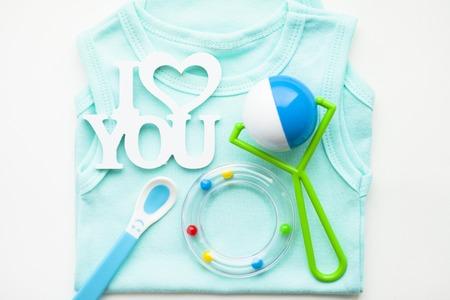 Newborn baby story. T-shirt and children's toys, scissors, baby bottle, nipple, hairbrush on white background. Top view