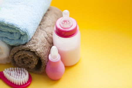 Newborn baby story. Towels and children's toys, scissors, baby bottle, nipple, hairbrush on yellow background. Top view 스톡 콘텐츠