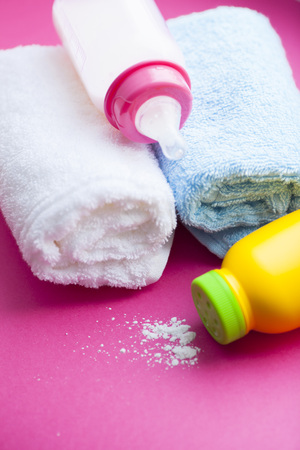 Newborn baby story. Towels and children's toys, scissors, baby bottle, nipple, hairbrush on red background. Top view