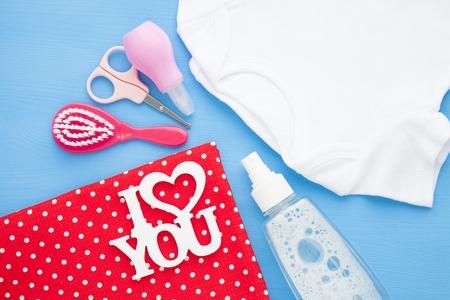 Newborn baby story. Children's toys, scissors, baby bottle, nipple, hairbrush on red background. Top view