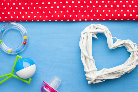 Newborn baby story. Strow heart and children's toys, scissors, baby bottle, nipple, hairbrush on blue background. Top view