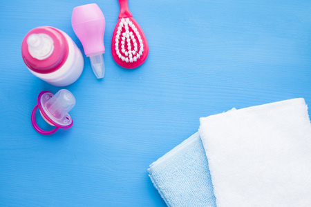 Newborn baby story. Towels and children's toys, scissors, baby bottle, nipple, hairbrush on blue background. Top view 스톡 콘텐츠
