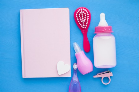 Newborn baby story. Notepad with copyspace and children's toys, scissors, baby bottle, nipple, hairbrush on blue background. Top view