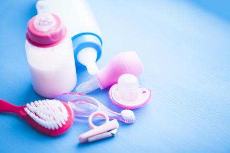 Newborn baby story. Children's toys, scissors, baby bottle, nipple, hairbrush on blue background. Top view