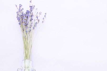 Spa and wellness setting with lavender flowers, sea salt, oil in a bottle, aroma candle on wooden white background closeup Banco de Imagens