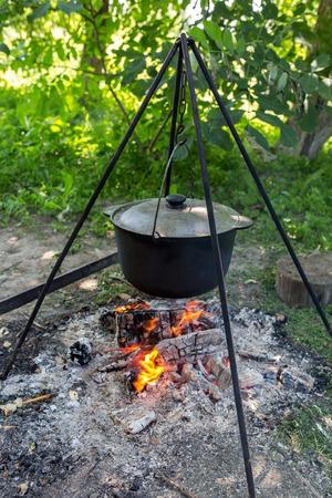 Black pot heated on a tripod over a campfire