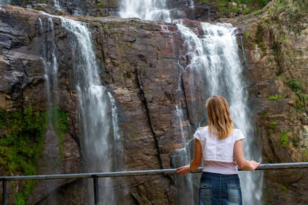 A girl stands in front of a waterfall and admires the beautiful view