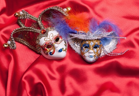 Two venetian mask on a red silk photo