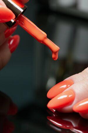 Fragment of a woman's hand, painted nails. Nail polish brush.