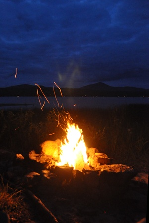 hearthside: Flames of a fire shoot sparks skyward, blue mountains in background