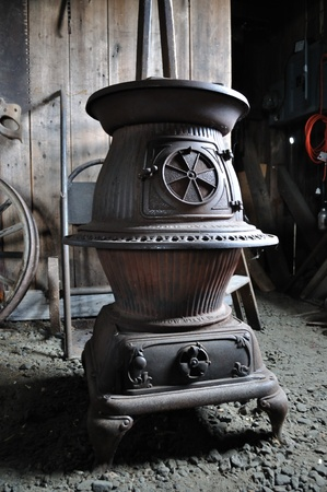 Graceful scrolled ironwork rings the potbelly of this antique woodstove in a blacksmith's shop. Stock Photo