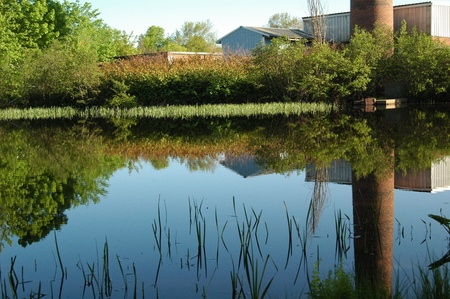 Brick Tower reflected in glass-calm rural pond Stock Photo