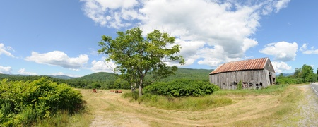 Panoramic barn in mountain valley hayfield