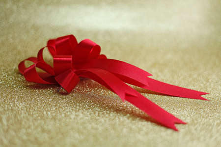 edel: Christmas red bow on background in gold Stock Photo