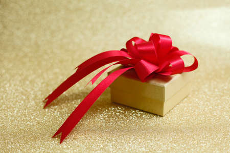 edel: Christmas gift on Decorative background in gold with sparkling stars Stock Photo