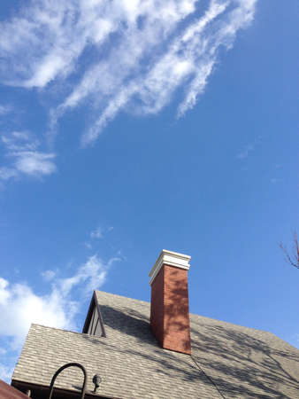 pitched roof: Roof with a chimney On beautiful sky Stock Photo