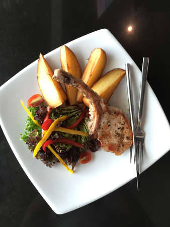 Grilled pork steak with tomato salad