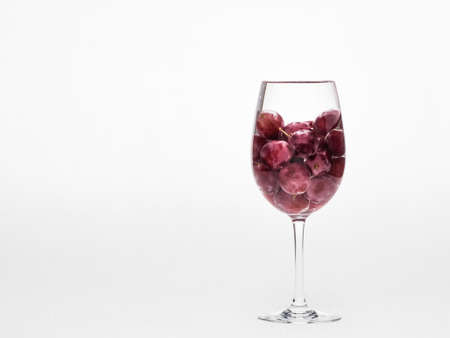 Half a wine glass of red grapes photo