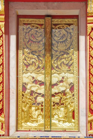 Arch windows with ornamental designs carved in the golden temple of Thai architecture. photo