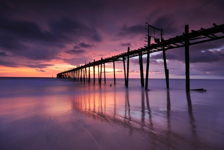 Filed wooden Pier into the sea after sunset on the beach