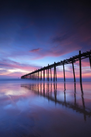 Filed wooden bridge into the sea after sunset on the beach