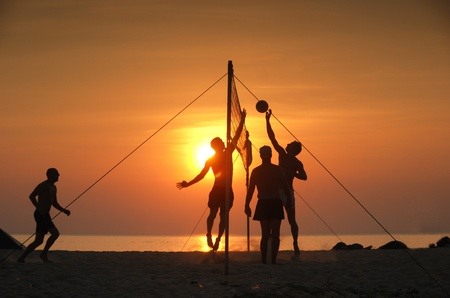 guy on beach: Beach volleyball. Is a popular sport that is played on the beach and playground sand