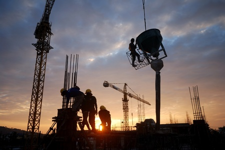 construction workers: Black silhouette of the building construction is not finished. Stock Photo