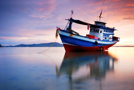 fisherman on boat: Thai fishing boat used as a vehicle for finding fish in the sea.at sunset
