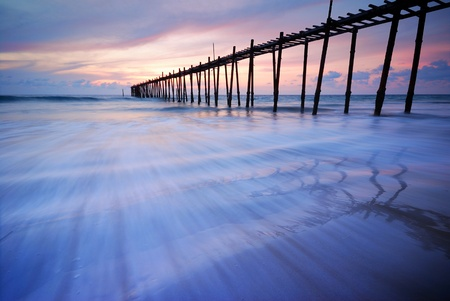 Filed wooden bridge into the sea after sunset on the beach photo