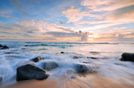 wschód słońca: Fale chłostać morze, rock, wpływ linii na plaży Zdjęcie Seryjne