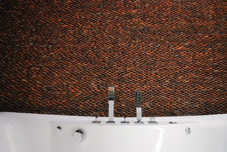 pebble stone wall bathroom with bathtub photo