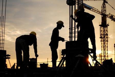 obreros trabajando: silueta de constructionworker en constructionsite Foto de archivo