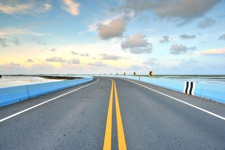 asphalt road to horizon in cloudy sky  photo