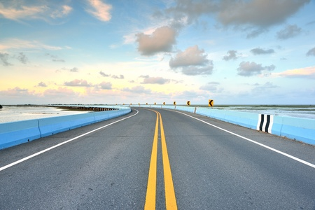 roadway: asphalt road to horizon in cloudy sky