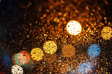 clean street: drops of rain on window with bokeh lights abstract