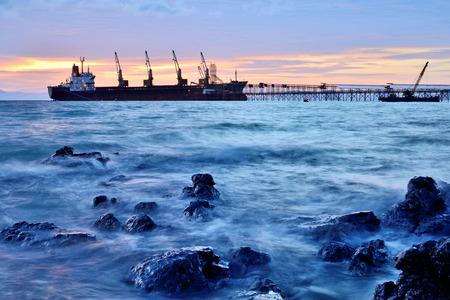 Reusachtig containervrachtschip bij zonsondergang