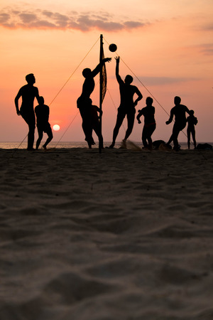 volleyball: silhouette of beach Volleyball player on the beach and playground sand in sunset
