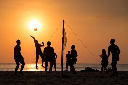 pelota de voleibol: silueta del jugador de voleibol de playa en la playa y un parque de arena en la puesta del sol