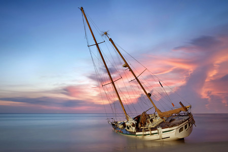 sailboat wreck in sea on the sand beach at sunset time Standard-Bild