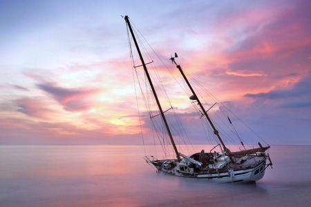ship wreck: sailboat wreck in sea on the sand beach at sunset time Stock Photo