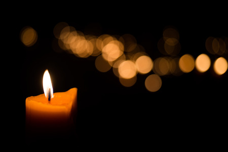 funeral background: Candle flame light at night with bokeh on dark background Stock Photo