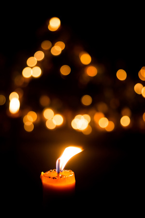 candles in dark: Candle flame light at night with bokeh on dark background Stock Photo