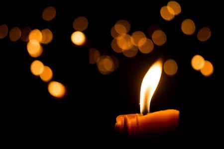 luz de velas: Una vela llama luz por la noche con bokeh sobre fondo oscuro