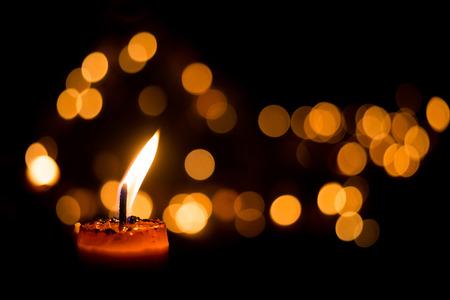 Una vela llama luz por la noche con bokeh sobre fondo oscuro