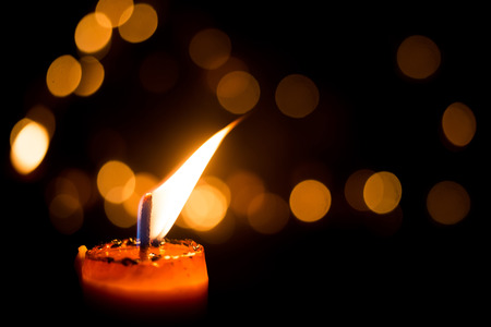 funeral background: One candle flame light at night with bokeh on dark background