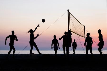 pelota de voley: silueta del jugador de voleibol de playa en la playa y un parque de arena en la puesta del sol