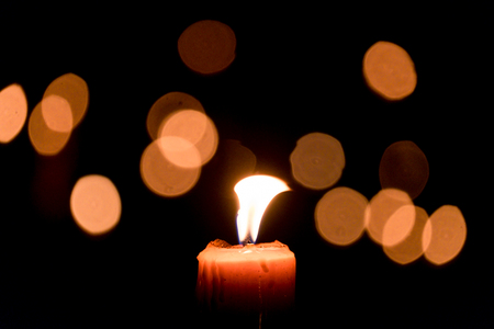 Candle flame light at night with bokeh on dark background Stock Photo